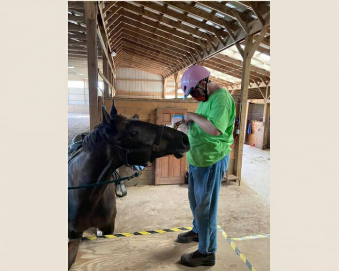 Athelas rider giving treats to her horse.