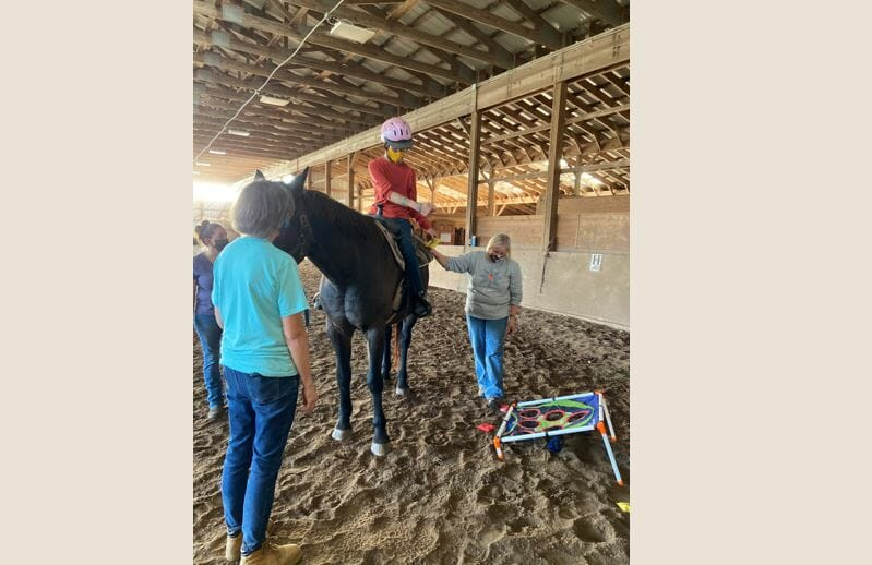 Athelas rider and two volunteers playing bean bag toss off their horse