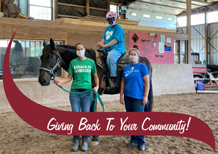 """Two volunteers with an Athelas horseback rider, maroon waving that says """"giving back to your community"""""""