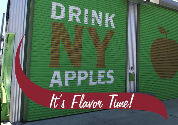 Drink NY Apples It's Flavor Time. A garage door in an urban setting.