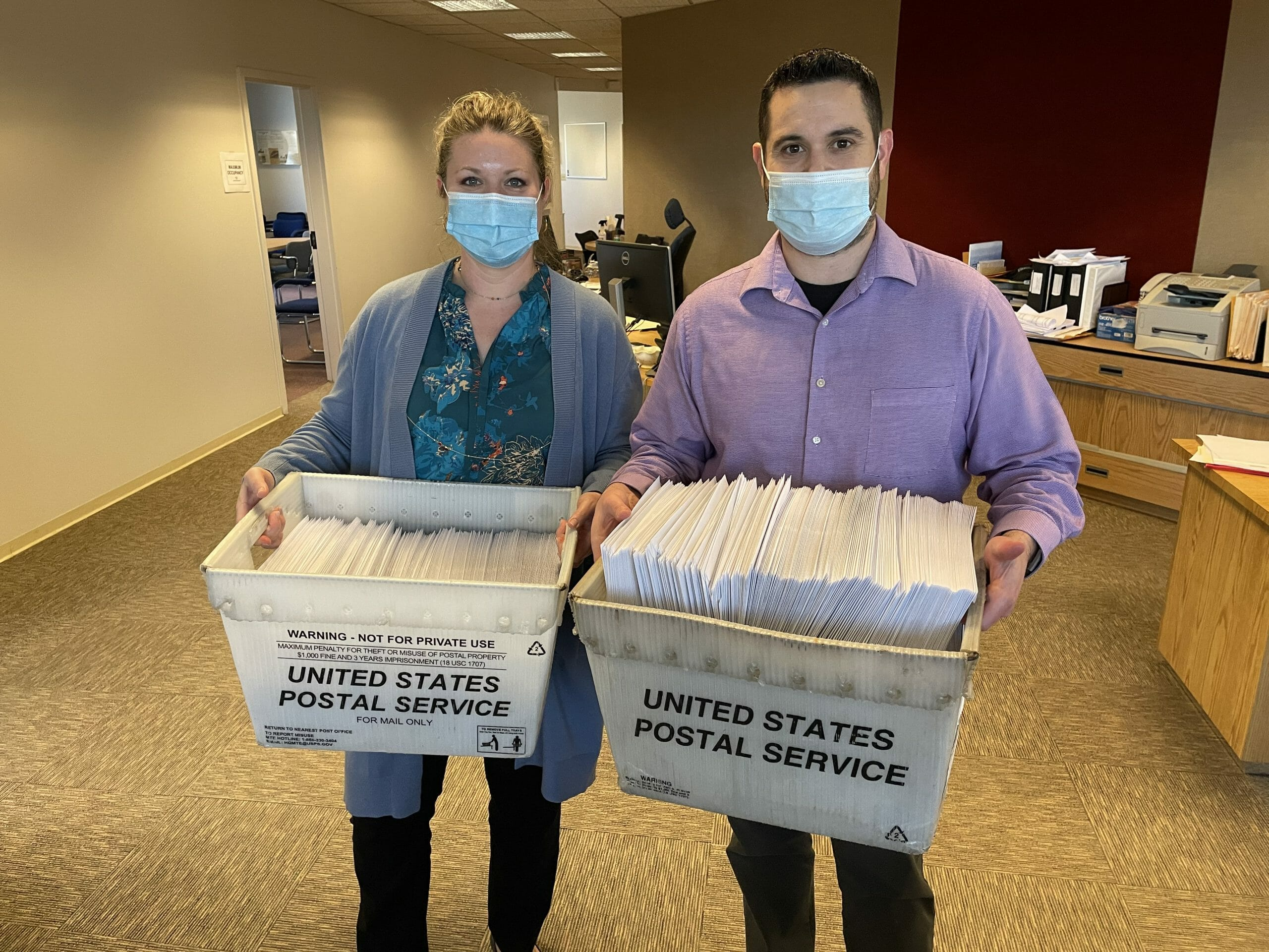 Donations team members with bins of holiday match checks