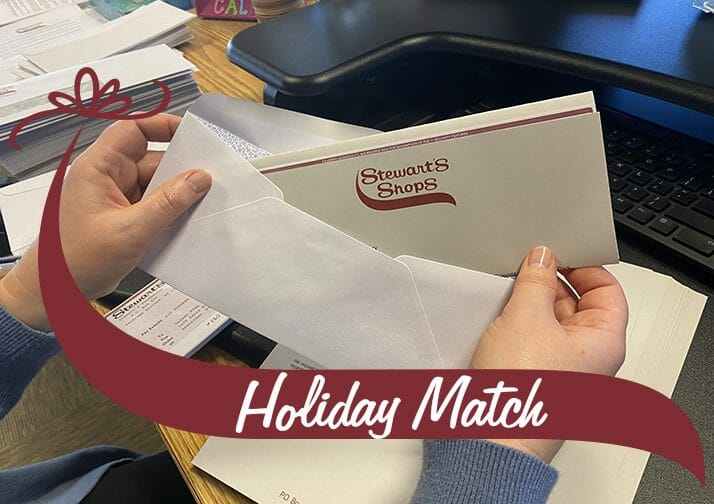 Stuffing a holiday match check into an envelope. Holiday Match wave.
