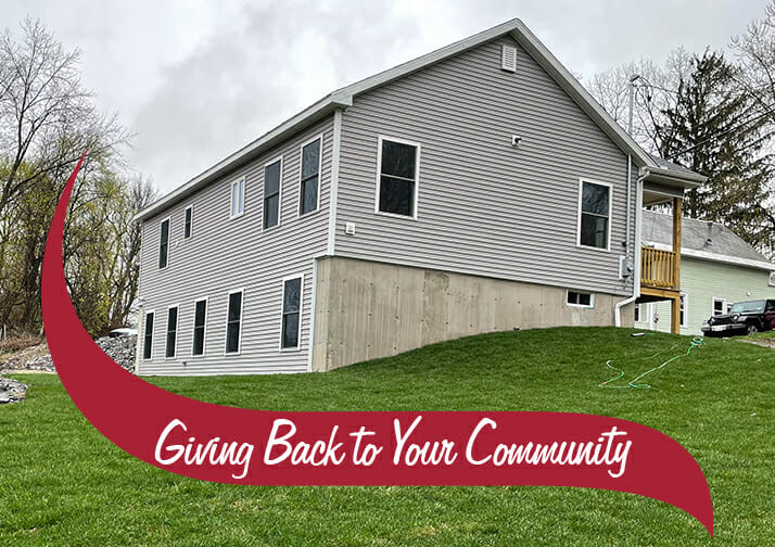 The back of a grey house with a nice green lawn. Giving back to your community.