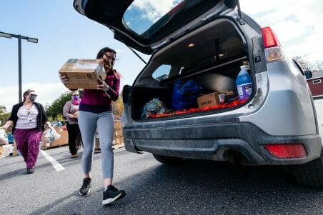 a woman carrying a box of food to an open trunk of a car