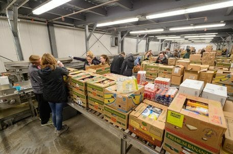a wide shot of a food pantry with people packing food.